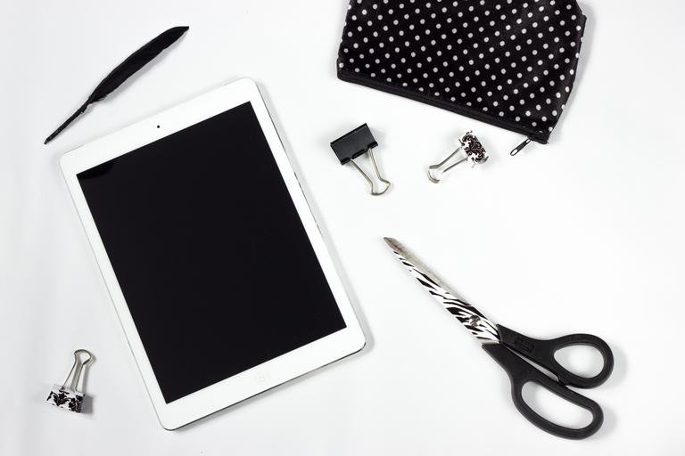 tablet work desk a pair of scissors a feather ipad electronic equipment black and white office accessories